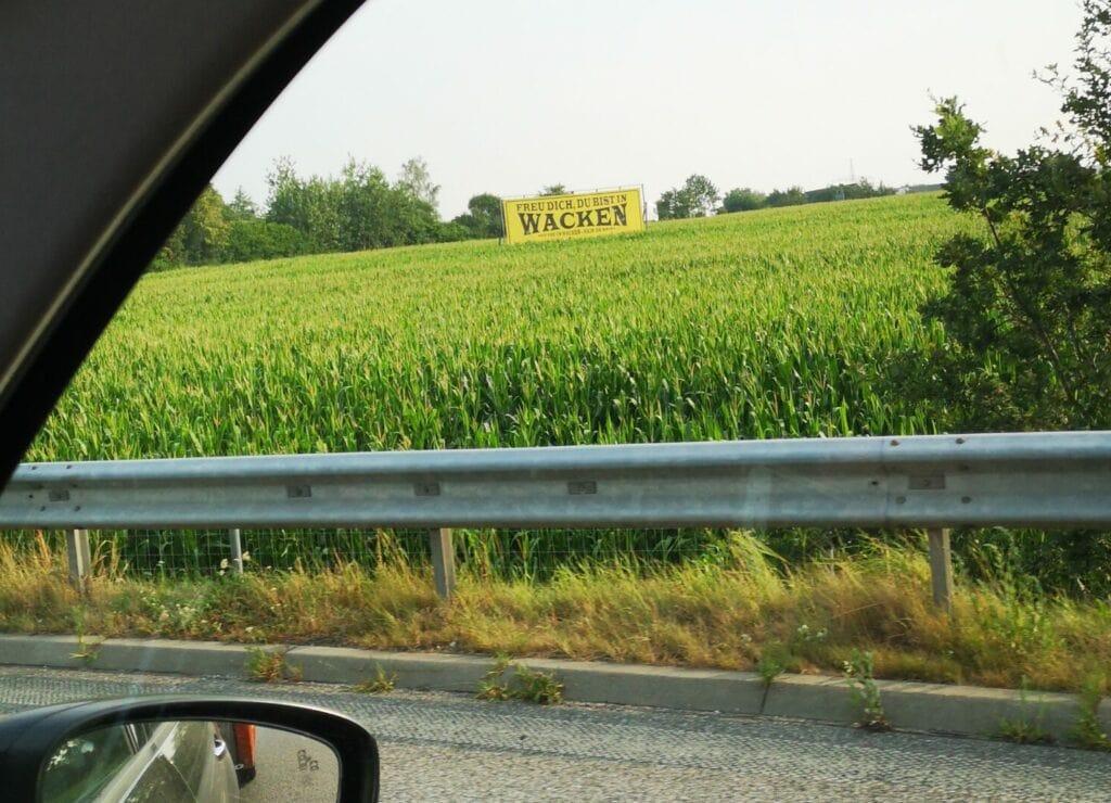 Aus dem Auto ein Wacken-Schild neben der Autobahn