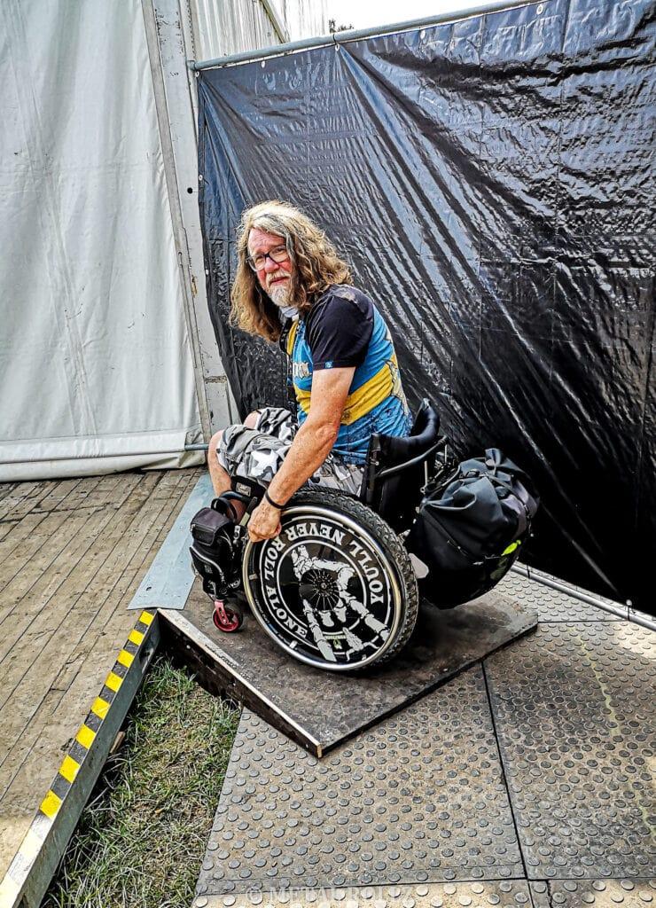 Ich stehe mit dem Rollstuhl auf einer kleinen Rampe.